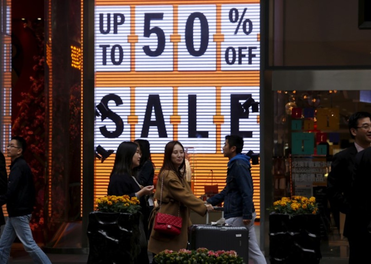 Shoppers walk past a store advertising discount rates in Tsim Sha Tsui, Hong Kong. Photo: Reuters / Bobby Yip