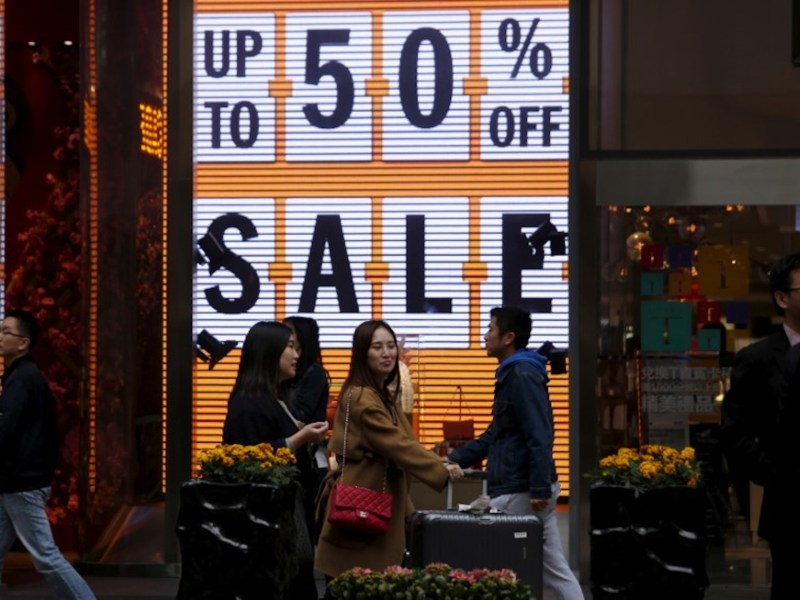 Shoppers walk past a store advertising discount rates in Tsim Sha Tsui, Hong Kong. Photo: Reuters / Bobby Yip