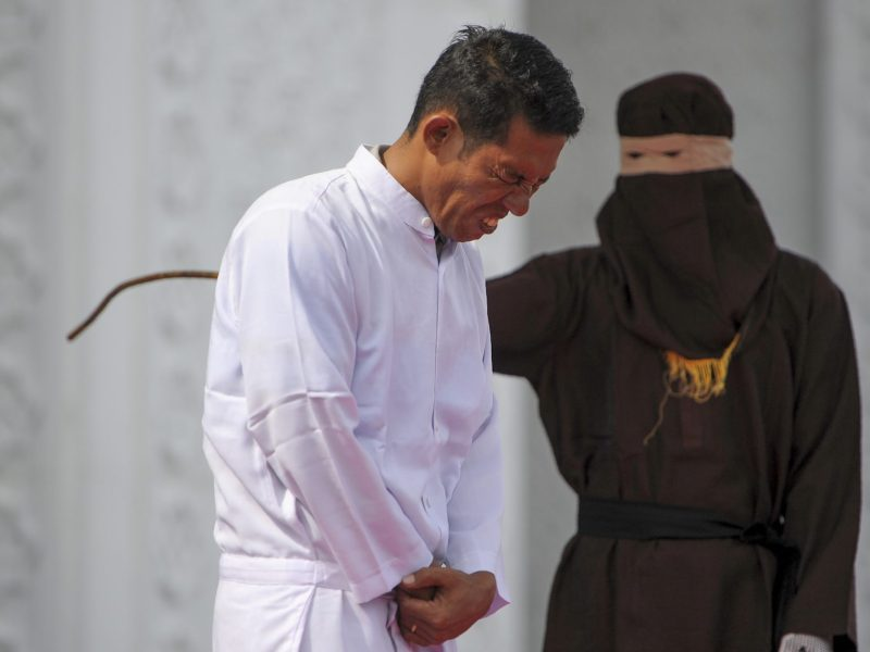 Jono Simbolon (front), an Indonesian Christian, grimaces in pain as he is flogged in front of a crowd outside a mosque in Banda Aceh, Aceh province, on January 19, 2018. Photo: AFP/Chaideer Mahyuddin