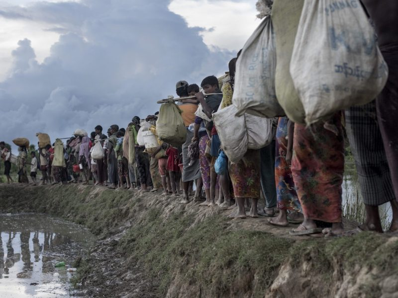 "(FILES) In this file photo taken on October 9, 2017 Rohingya refugees walk after crossing the Naf river from Myanmar into Bangladesh in Whaikhyang.Myanmar is continuing its ""ethnic cleansing"" of the Rohingya with a ""campaign of terror and forced starvation"" in Rakhine state, a UN human rights envoy said on March 6, 2018, six months after a military crackdown sparked a mass exodus of the Muslim minority. / AFP PHOTO / FRED DUFOUR"