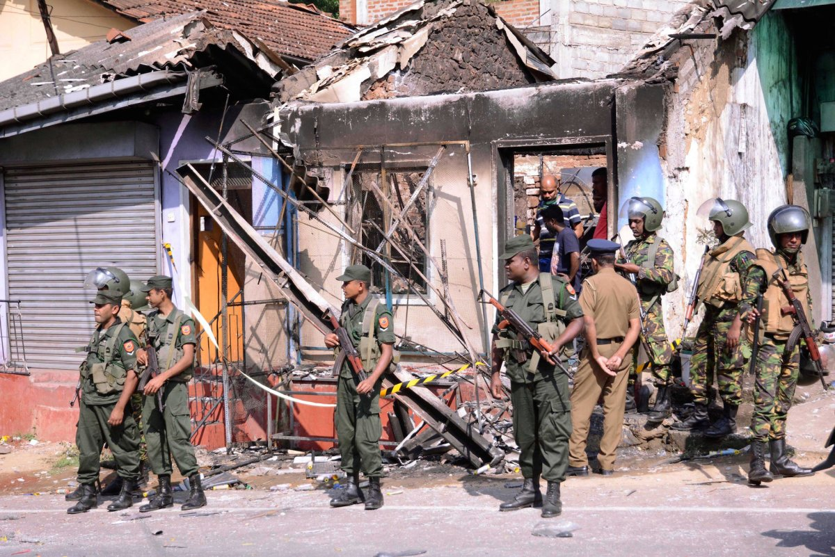 Sri Lanka's Special Task Force and police officers stand guard near a burnt house after a clash between two communities in Digana, in the central district of Kandy, Sri Lanka, on March 6, 2018. Photo: Reuters