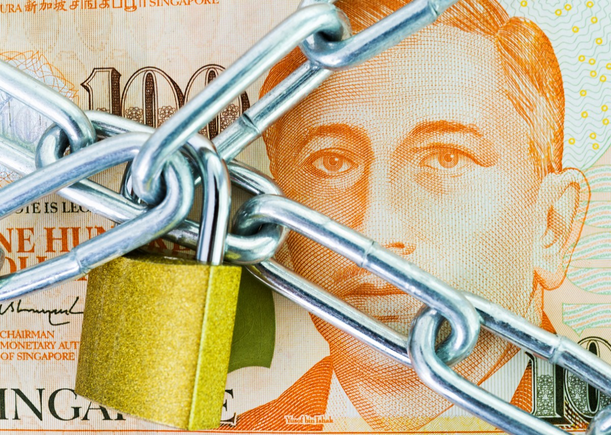 A Singapore currency note under lock and key. Image: iStock/Getty Images