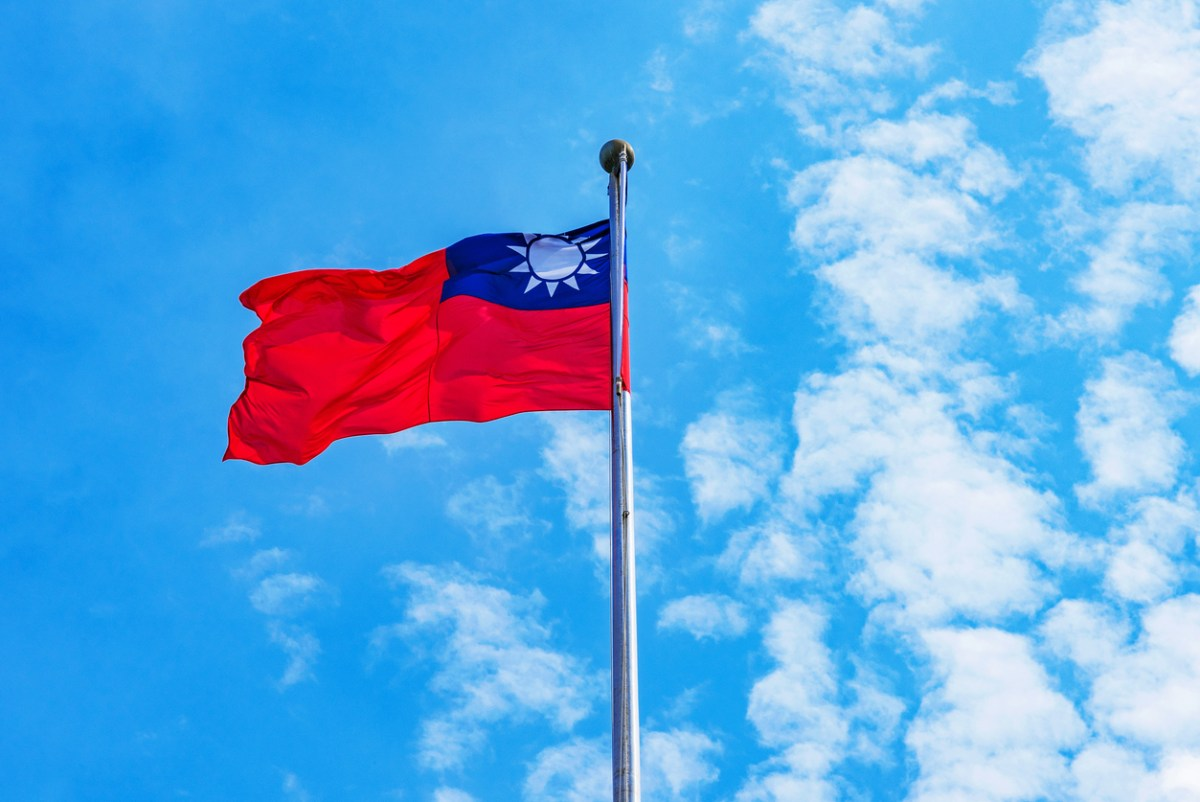 Taiwanese flag raised blowing in the wind with blue sky. Photo: iStock