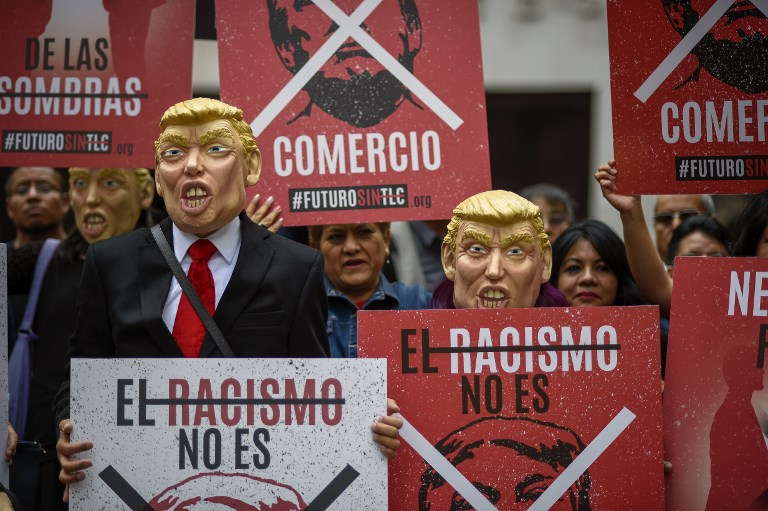 A group of Mexican labor union members don US President Donald Trump masks, during a protest against his economic policies and the North American Free Trade Agreement (NAFTA). Photo: AFP/Alfredo Estrella
