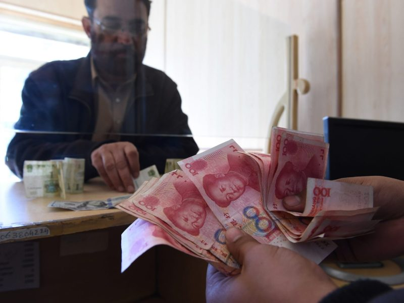 A Pakistani currency dealer counts Chinese yuan for a customer at his shop in Quetta on January 3. Officials now want to use the Pakistani rupee to pay for imports for a massive Chinese project. Photo: AFP/Banaras Khan
