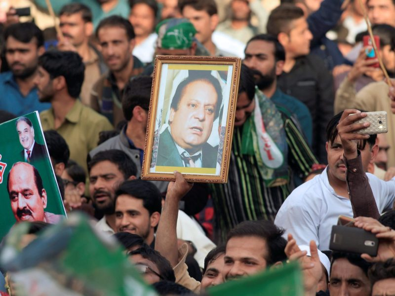 This file photo shows a supporter of Nawaz Sharif holding up his portrait. Pakistan's former PM was today sentenced to 10 years in prison for corruption.  Photo: Reuters