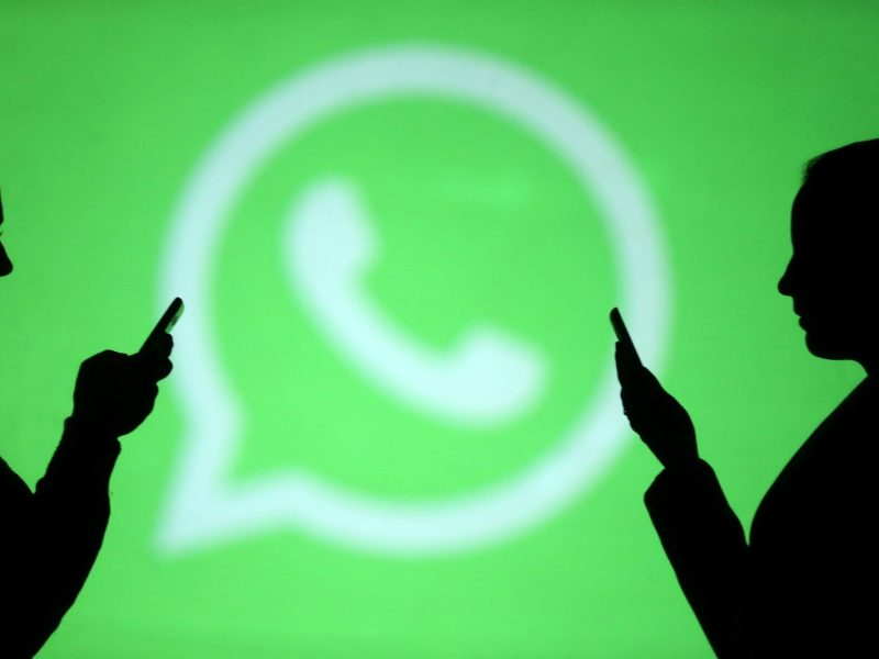Silhouettes of mobile users next to a screen projection of the WhatsApp logo. Photo: Reuters / Dado Ruvic