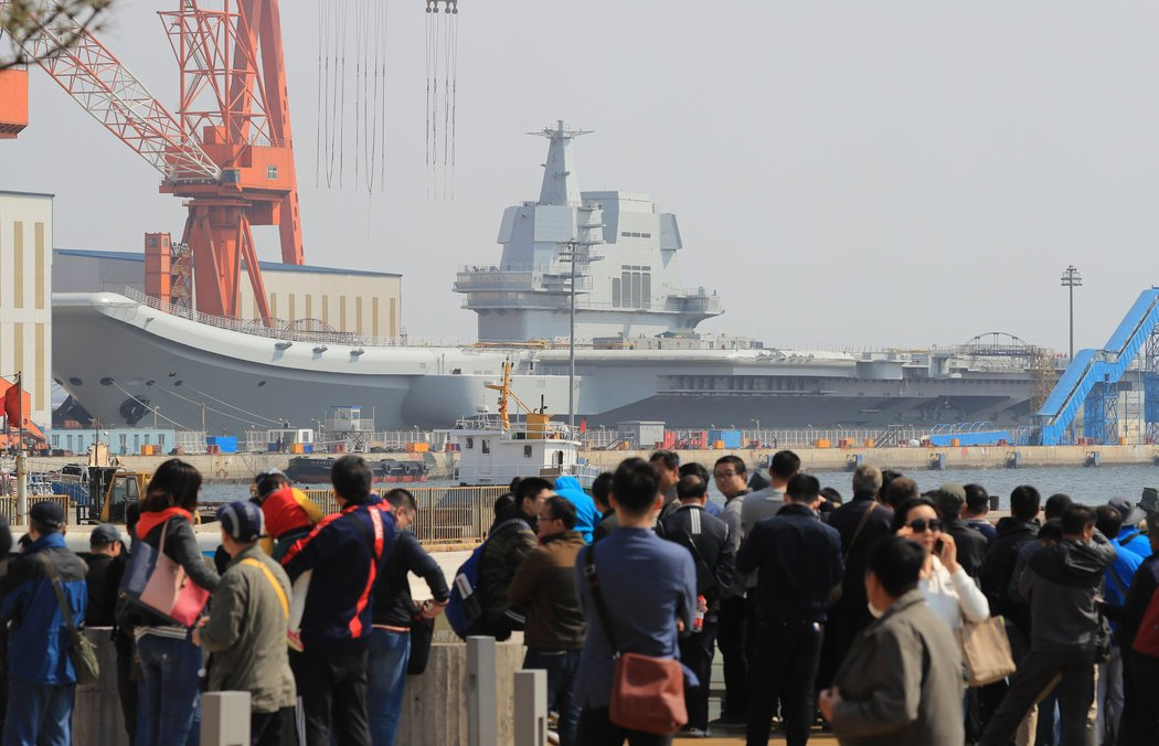 People gather near the berth of China's first domestically made aircraft carrier in Dalian. Photo: AP