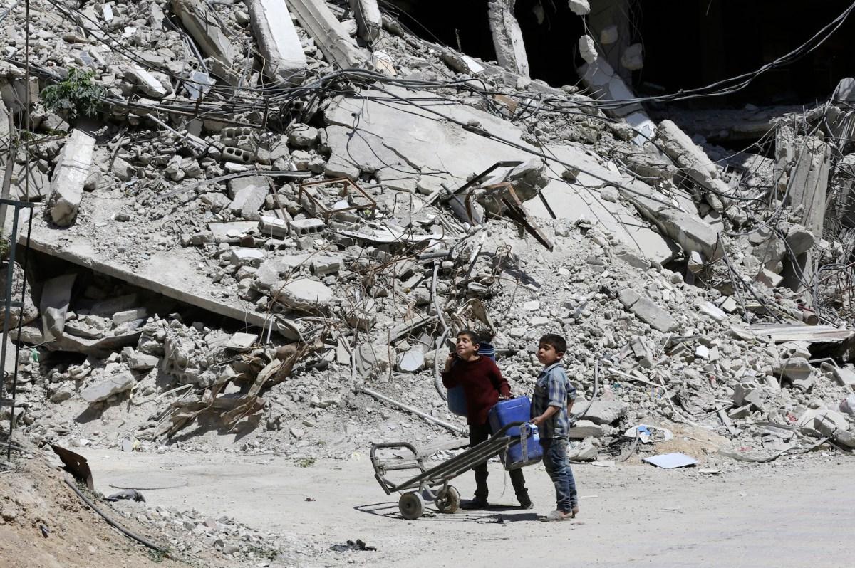 Syrian boys walk along a destroyed street in Douma on the outskirts of Damascus on April 16. Photo: AFP/Louai Beshara