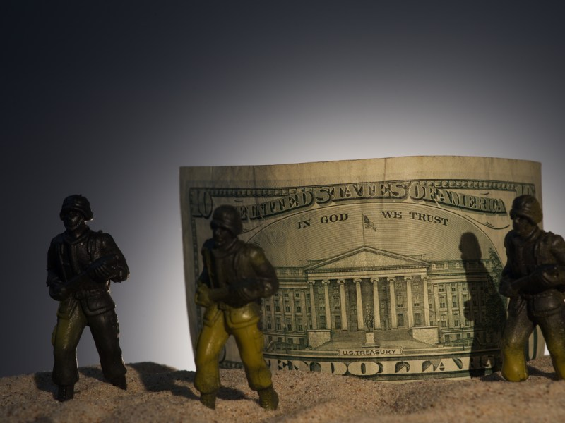Silhouette of military soldiers on money background.War, military and danger concept. Photo: iStock