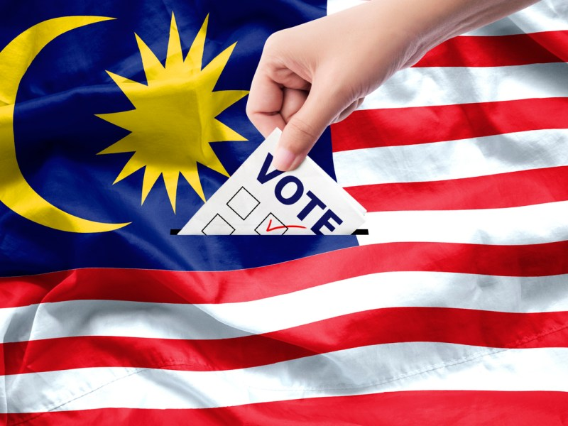 Malaysia general election concept. close up hand of a person casting a ballot at elections during voting on canvas Malaysia flag background. Photo: iStock