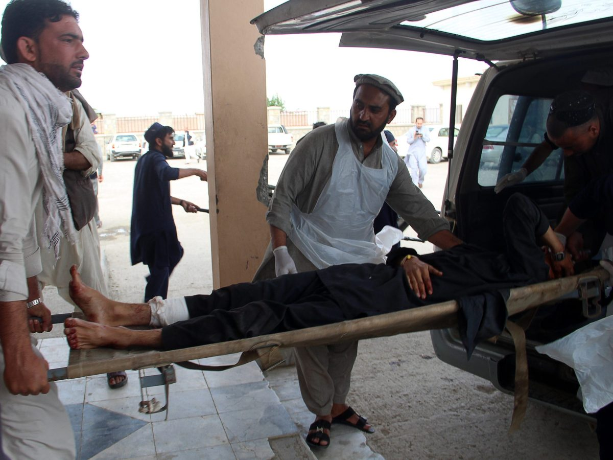 A wounded Afghan man lies on a trolley as others take him to a hospital after a blast at a voter registration center in Khost province on May 6, 2018.A blast at a voter registration centre in Afghanistan's restive east on May 6 killed or wounded at least 30 people, officials said, capping a bloody week in the war-torn country. Photo: AFP / Farid Zahir