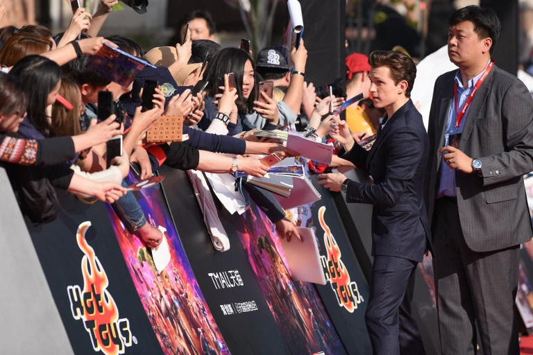 "English actor Tom Holland signs autographs for fans as he arrives on the red carpet of a promotional event for his new movie ""Avengers: Infinity War"" in Shanghai. Photo: AFP"