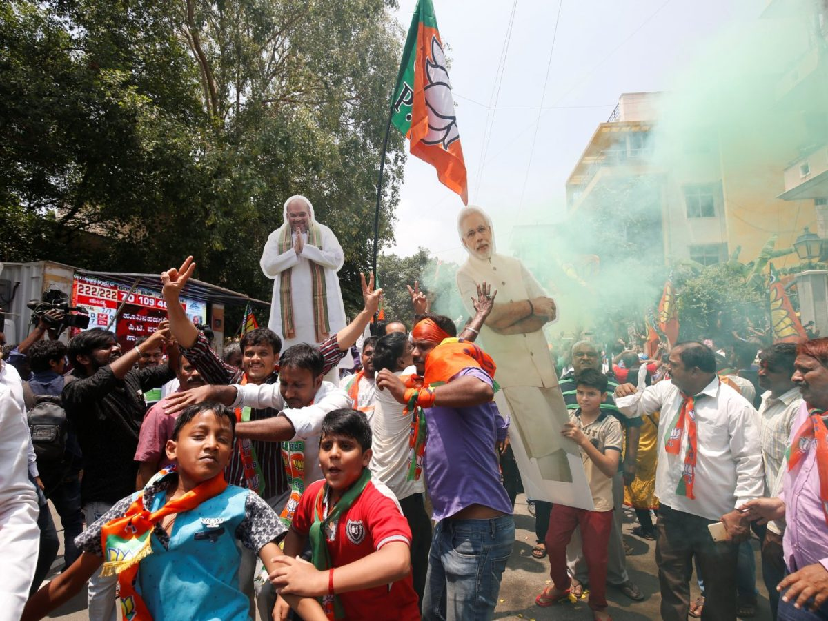 Supporters of India's ruling Bharatiya Janata Party celebrate as they carry cut-outs of party President Amit Shah and Prime Minister Narendra Modi after learning of the initial poll results in the Karnataka state assembly elections in Bengaluru, India, on May 15, 2018. Photo: Reuters/Abhishek N. Chinnappa