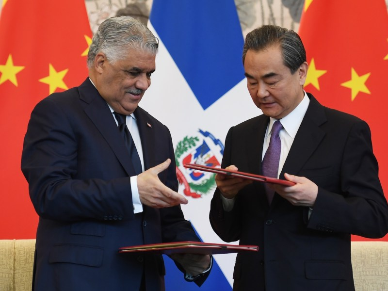 Dominican Republic Foreign Minister Miguel Vargas (L) and China's Foreign Minister Wang Yi exchange documents during a signing ceremony where they formally established relations, in Beijing on May 1, 2018. Photo: AFP/Greg Baker