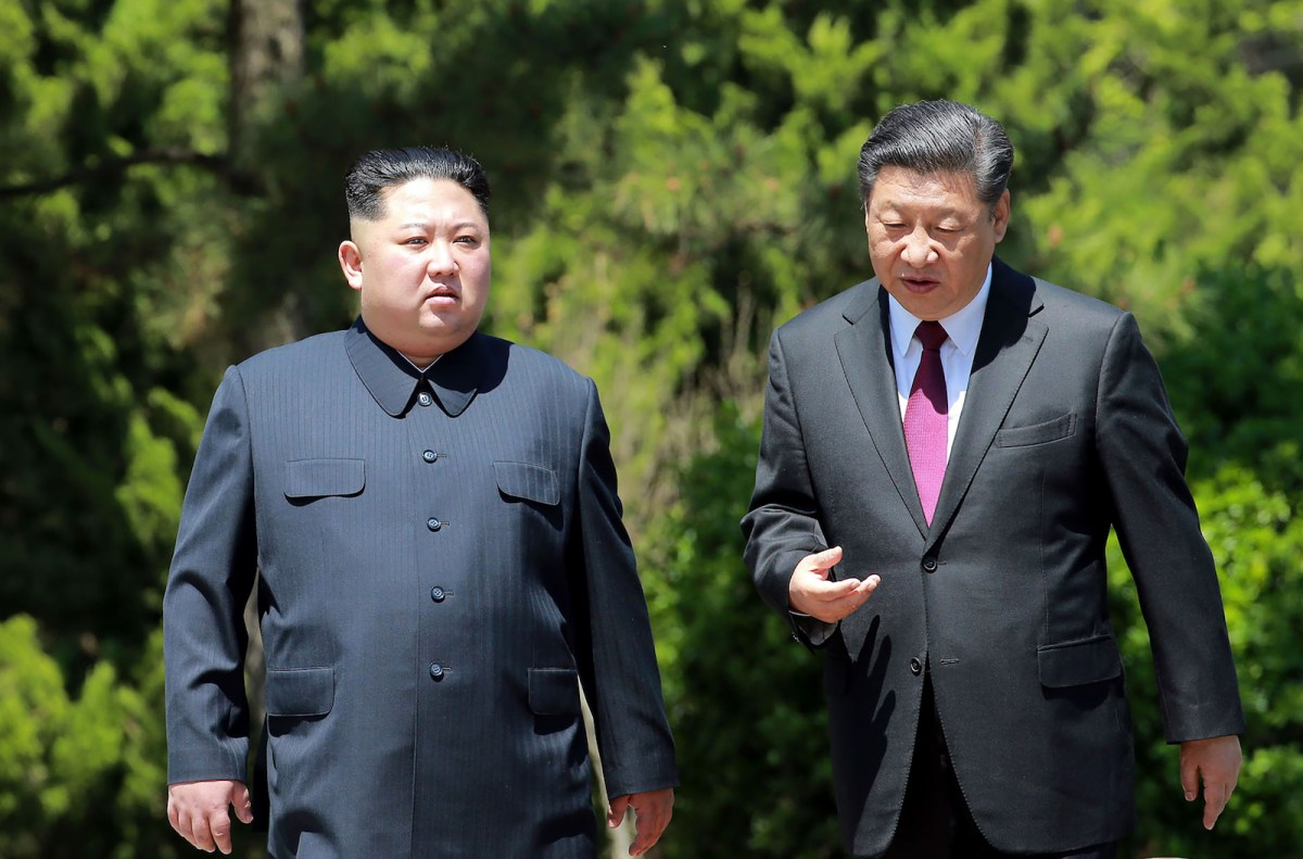 Chinese President Xi Jinping (right) walks with North Korean leader Kim Jong-un in the Chinese city of Dalian on May 8, 2018. Photo: KCNA via KNS and AFP