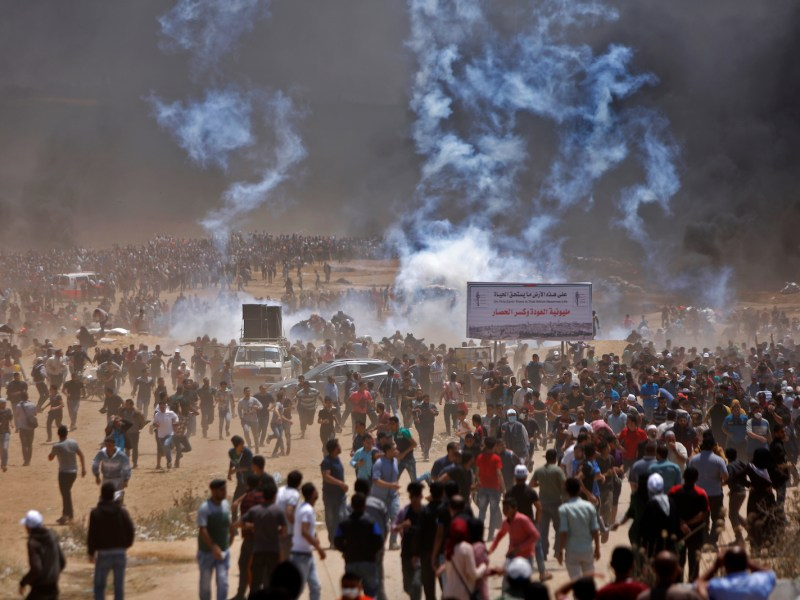 Palestinians run for cover from tear gas during clashes with Israeli security forces near the border between Israel and the Gaza Strip, east of Jabalia on May 14, 2018, as Palestinians protest over the inauguration of the US embassy following its controversial move to Jerusalem. Photo: AFP/ Mohammed Abed