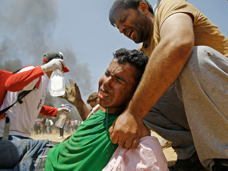 A Palestinian man assists a wounded protester during clashes with Israeli security forces near the border between Israel and the Gaza Strip, east of Jabalia on May 14, 2018, as Palestinians protest over the inauguration of the US embassy following its controversial move to Jerusalem. Photo: AFP/ Mohammed Abed