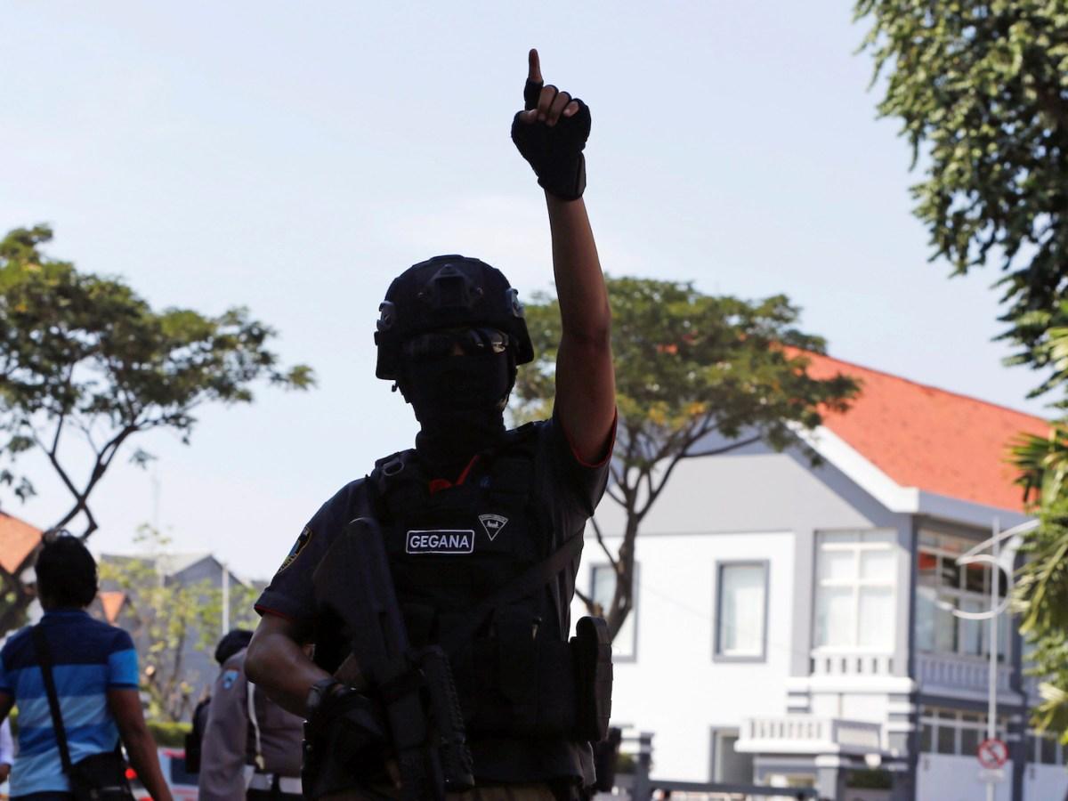 Anti-terror policemen stand guard following a bomb blast at police office in Surabaya, Indonesia May 14, 2018. Photo: Reuters/Beawiharta