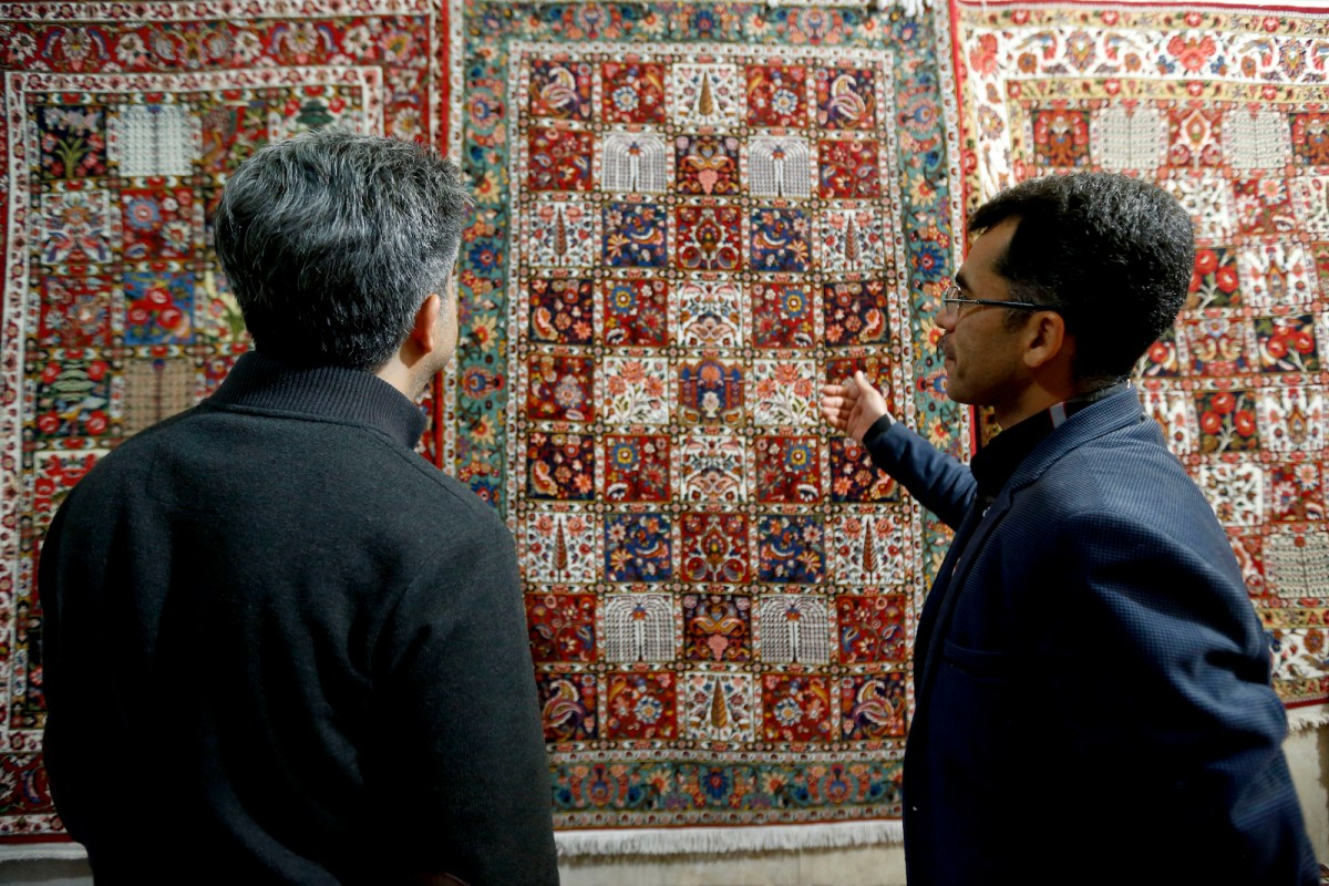 Two men bargain over the price of a carpet in a bazaar in Iran, but would Donald Trump cut a better deal? Photo: AFP/Atta Kenare