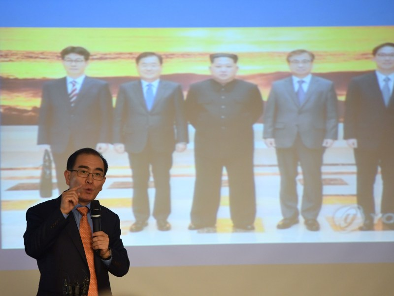 Thae Yong-ho, who fled his post as North Korea's deputy ambassador to Britain in August 2016, speaks as a picture of North Korean leader Kim Jong-un with South Korean envoys is seen on a screen during a press conference for his memoir in Seoul on May 14, 2018. Photo: AFP/Jung Yeon-je
