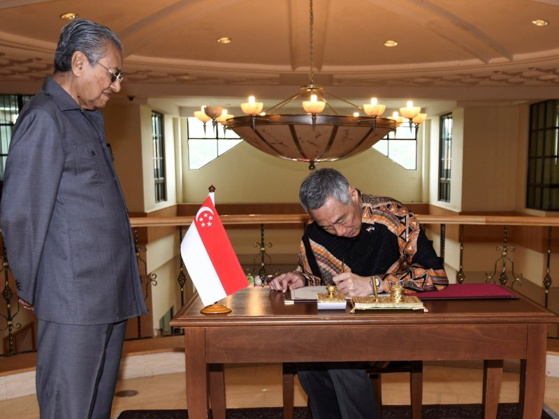 Singapore's Prime Minister Lee Hsien Loong signs a guestbook next to Malaysia's Prime Minister Mahathir Mohamad prior to their private meeting in Putrajaya, Malaysia, May 19, 2018. Department of Information via Reuters/Hafiz Itam