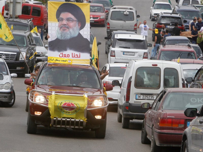 A man gestures as he drives a car with the picture of Hezbollah leader Sayyed Hassan Nasrallah on it, on election day in Bint Jbeil in southern Lebanon on Sunday. Photo: Reuters/Aziz Taher