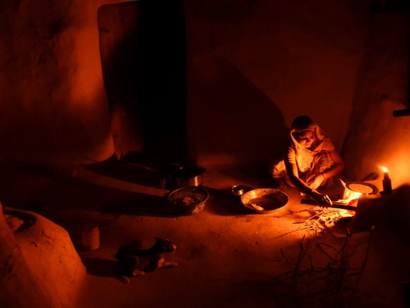 An Indian woman cooks food by candlelight in her home in the village of Anandpur in the northern state of Uttar Pradesh. Photo: AFP/Money Sharma