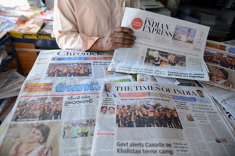 An Indian shop vendor displays newspapers. Madras court says mag can't publish anything about MP's family without providing similar space for a rebuttal. Photo: AFP/ Noah Seelam