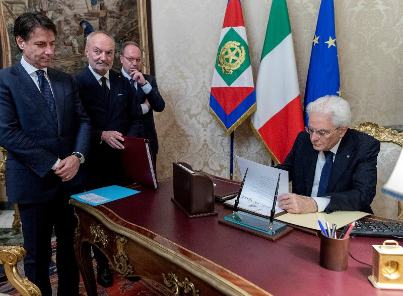 Italy's Prime Minister-designate Giuseppe Conte looks on as Italian President Sergio Mattarella signs documents at the Quirinal Palace in Rome on Thursday. Italian Presidential Press via Reuters