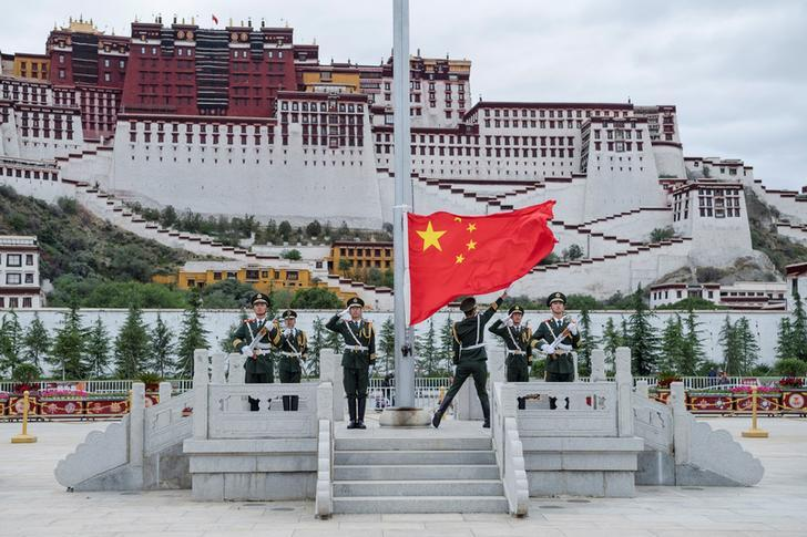 Chinese paramilitary police raise a Chinese flag in front of the Potala Palace, once the residence of the Dalai Lama, in the Tibetan capital Lhasa. Photo: China News Service