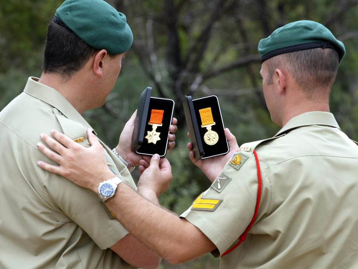 Two Australian commandos - part of a special forces troop that were pulled out of Afghanistan - look at their medals of honor for their military service in a file photo.  Photo: AFP/Troy Bendeich