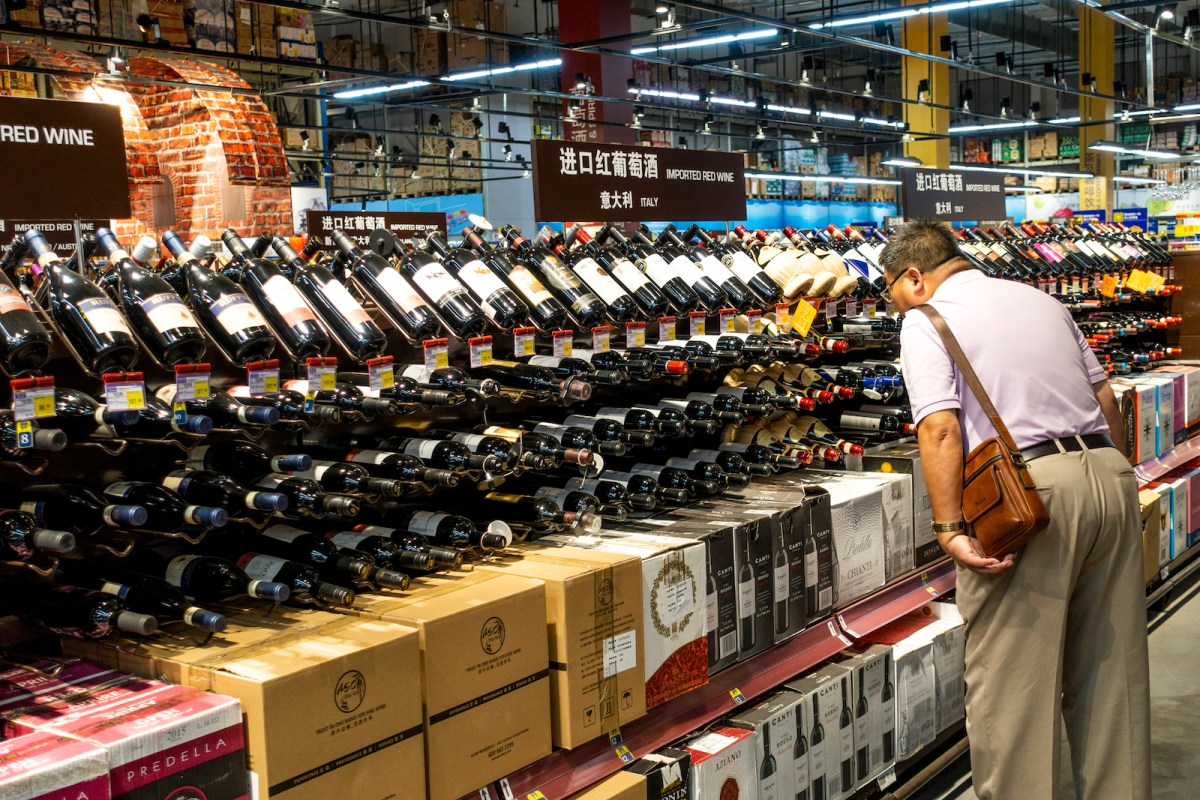 A lone customer shops for red wine at a Metro Supermarket in Shanghai. Chinese retail sales dropped in May. Photo: AFP