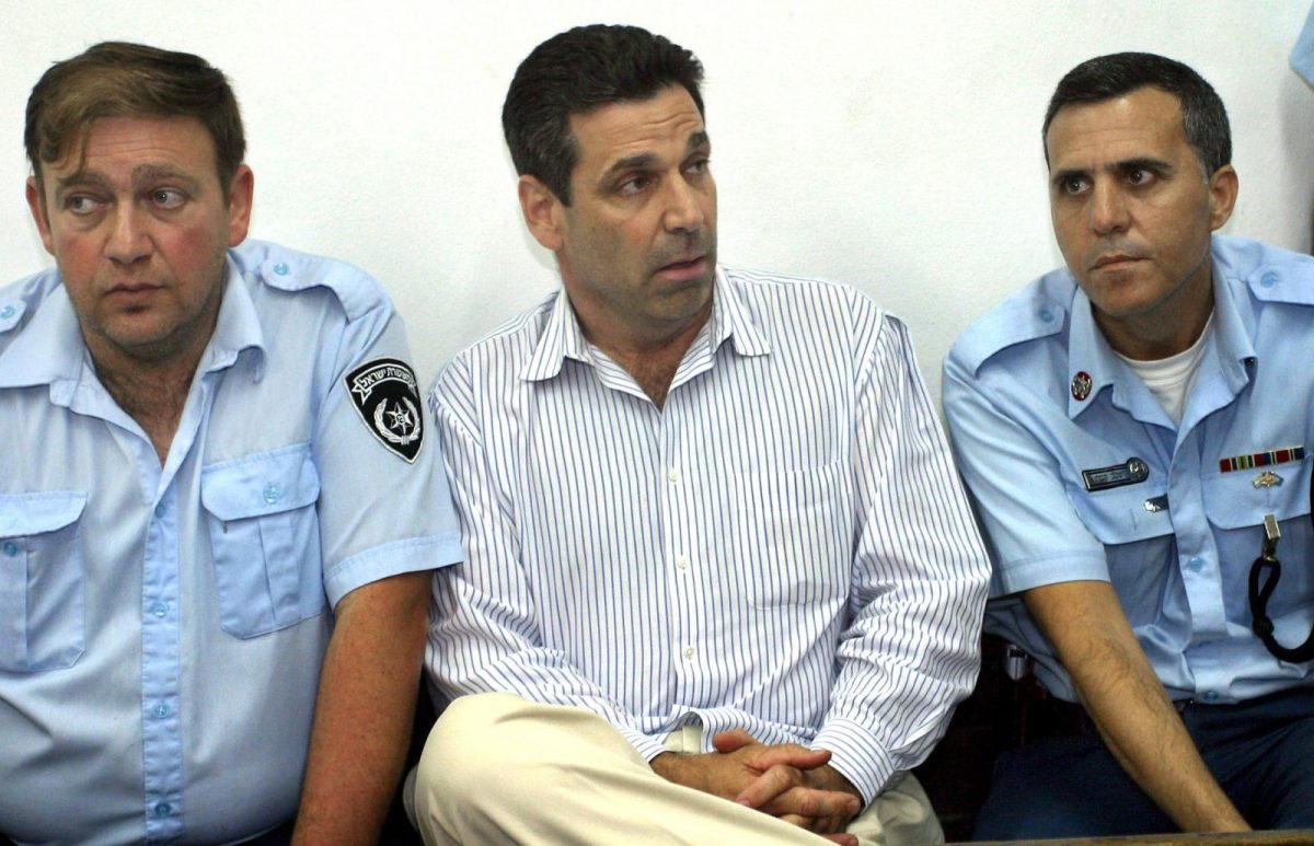 On April 22, 2004, Former Israeli energy minister Gonen Segev (C) appeared at the Tel Aviv district tribunal after being arrested for drug trafficking. He has now been charged with spying for Iran. Photo: AFP/Yariv Hatz