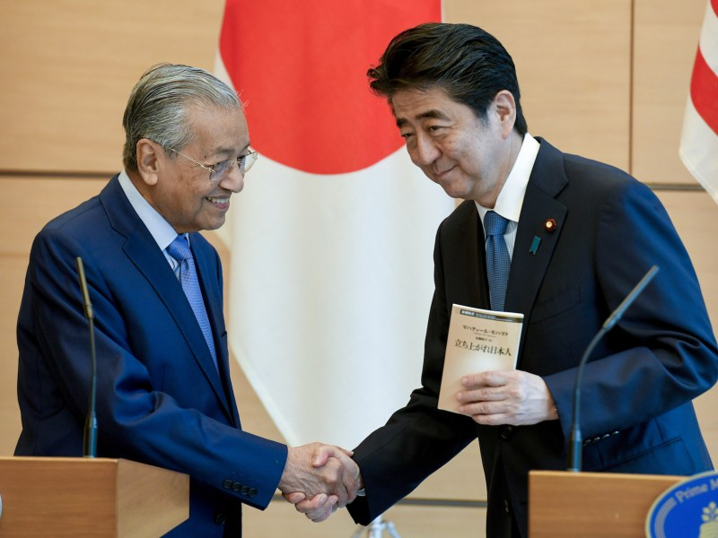 Japan's Prime Minister Shinzo Abe (R) and Malaysia's Prime Minister Mahathir Mohamad shake hands during joint press remarks at Abe's official residence in Tokyo on June 12, 2018. Photo: AFP/Pool/  Toshifumi Kitamura