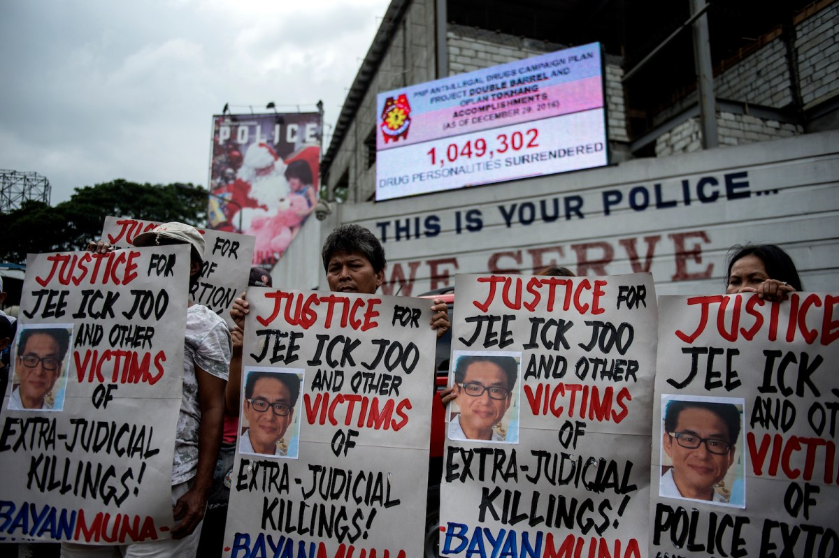 Activists hold a protest in front of Camp Crame, the headquarters of the Philippine National Police (PNP), carrying mock dead bodies, condemning the government's War on Drugs and holding placards showing the picture of the late South Korean businessman Jee Ick-Joo, who was murdered allegedly by suspected policemen in Manila on January 27, 2017.The South Korean businessman was allegedly kidnapped by Philippine policemen under the guise of a raid on illegal drugs and murdered at the national police headquarters in Manila, authorities said on January 18. / AFP PHOTO / NOEL CELIS
