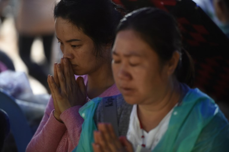 Relatives pray as they keep vigil in Khun Nam Nang Non Forest Park near Than Luang cave in Chiang Rai province on June 28, 2018 while rescue personnel conduct operation for a missing children's soccer team and their coach. Photo: AFP / Lillian Suwanrumpha