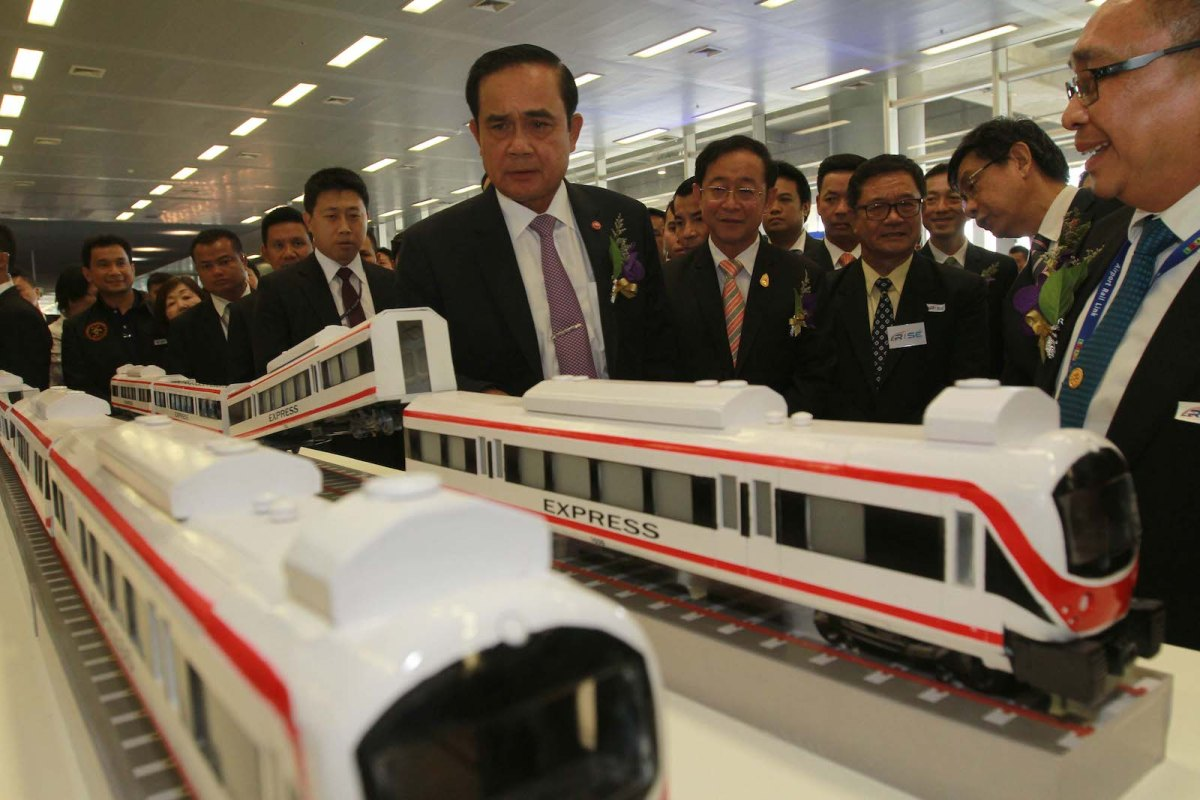 Thai Prime Minister Prayut Chan-ocha looks at a model train that he had picked up and left derailed after delivering a speech to open the Second Thai Rail Industry Symposium and Exhibition at the Airport Rail Link Makkasan station, March 16, 2016. Photo: AFP Forum