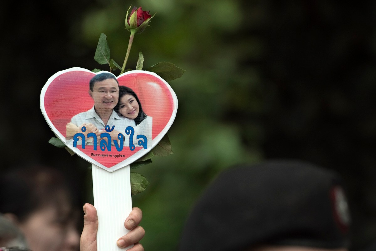 A supporter of deposed former Thai premiers Thaksin and Yingluck Shinawatra holds a small heart-shaped placard with their pictures. Photo: AFP/   Nicolas Asfouri