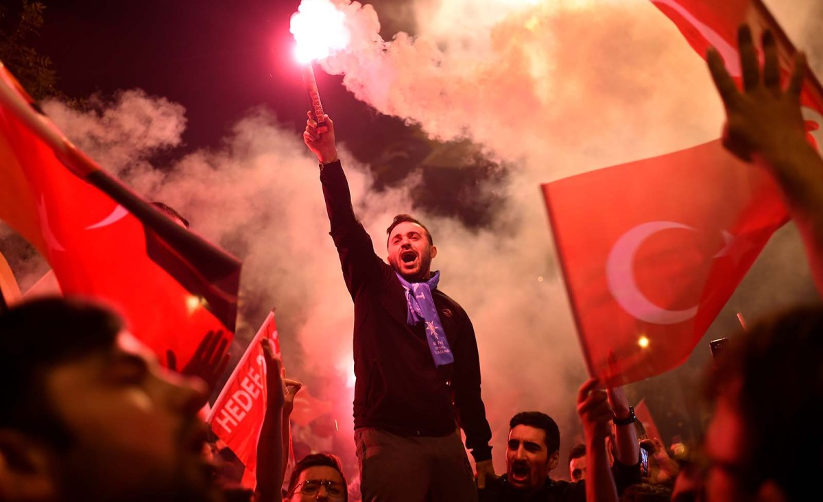 A crowd shouts slogans and while one man sets off a flare outside the Justice and Development Party (AKP) headquarters Istanbul on June 24, 2018, duringTurkey's presidential and parliamentary elections. Photo: AFP/Yasin Akgul