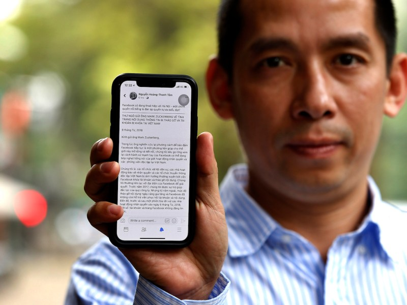Vietnamese activist La Viet Dung holds up a phone with the screen displaying an open letter to Facebook chief Mark Zuckerberg in Hanoi on April 10, 2018.Photo: AFP