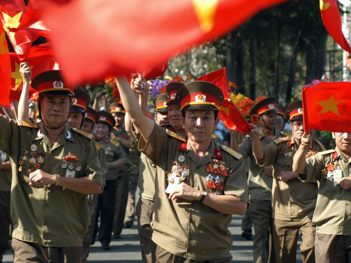 Vietnamese veterans march and wave flags during a parade held at the former presidential palace in Ho Chi Minh city to mark an anniversary of the Vietnam War's Tet 1968 offensive. Photo: AFP/Stringer