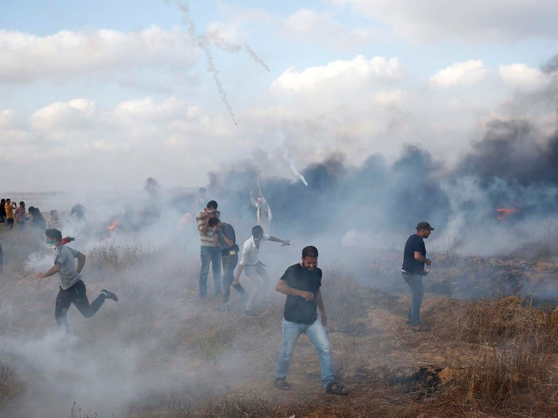 Palestinian protesters flee incoming tear gas canisters during clashes along the border with Israel in the southern Gaza strip on June 1, 2018. Photo: AFP/Said Khatib