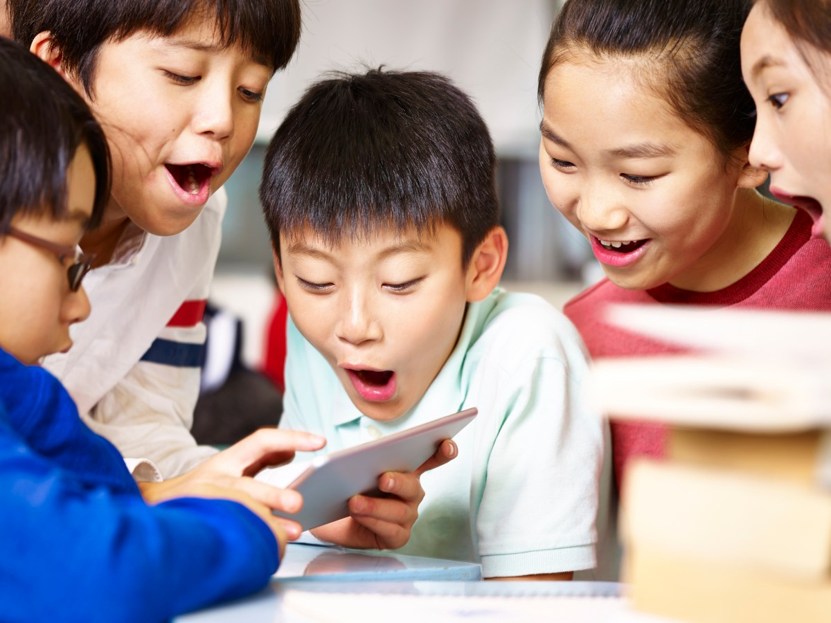 Group of Asian elementary school children gathering around playing game together using tablet during break. Photo: iStock