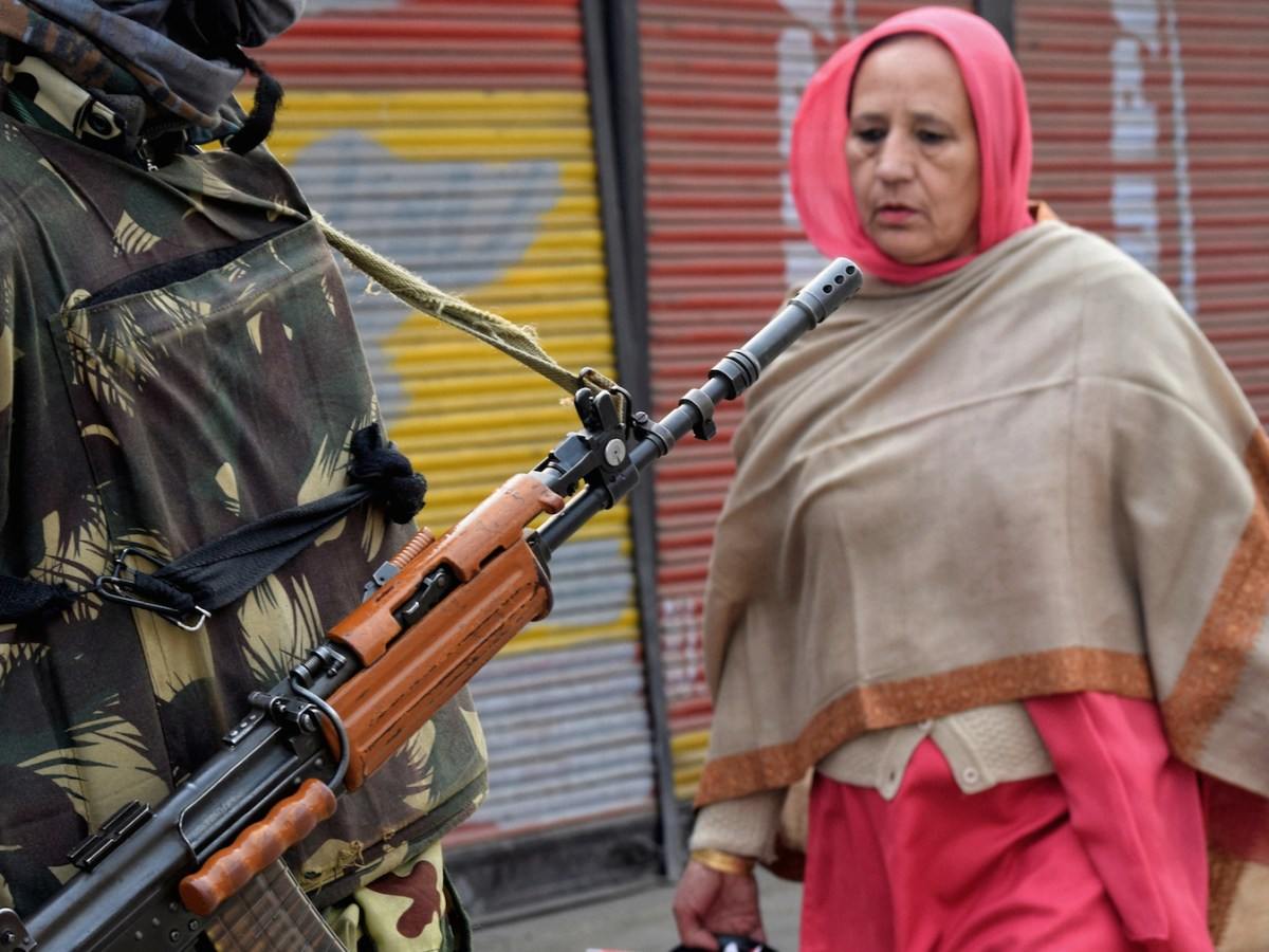 An Indian paramilitary trooper stands guard while a Kashmiri woman walks by in Srinagar, the summer capital of Kashmir. Photo: iStock/Bilal Ahmad