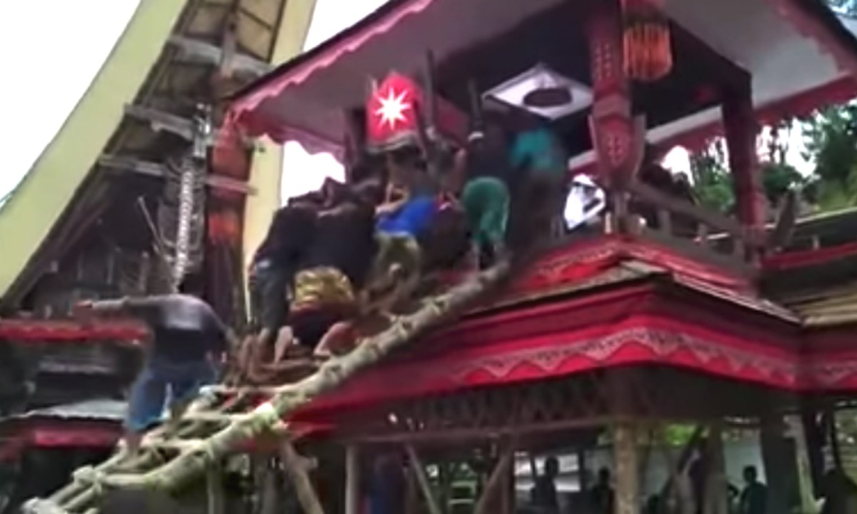 A man was hit on the head when the ladder collapsed and his mother's coffin landed on top of him. Photo: Kabar News, Youtube