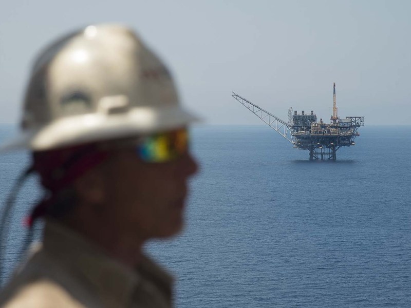 A worker on the Israeli Tamar platform in front of the Mari-B platform off the coast of Israel. Photo: AFP/Ahikam Seri