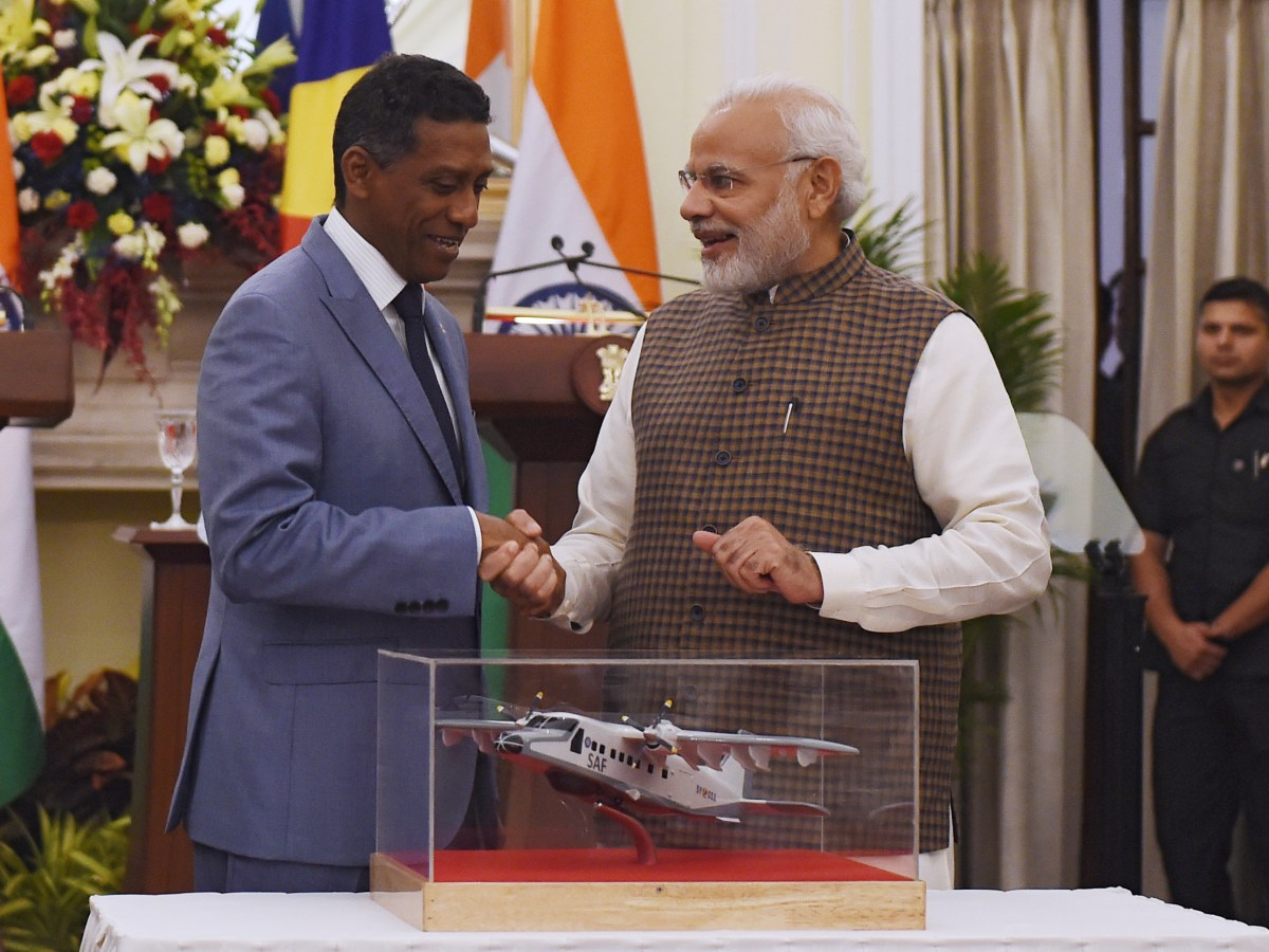 Indian Prime Minister Narendra Modi (R) shakes hand with Seychelles President Danny Faure after presenting a model of Dornier aircraft during a joint press statement at Hyderabad house in New Delhi on June 25, 2018.  India will be handing over a Dornier aircraft to Seychelles on June 26. / AFP PHOTO / MONEY SHARMA