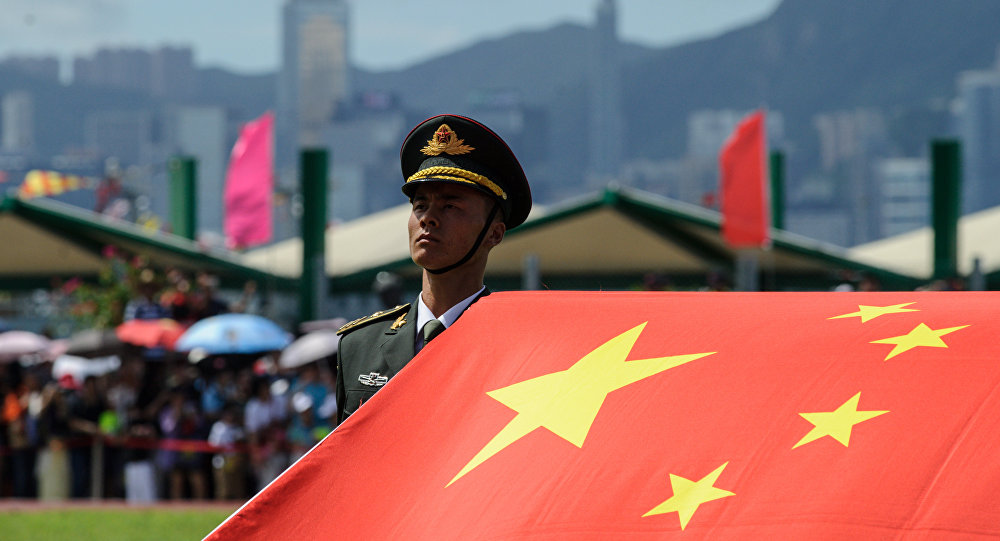 A PLA honor guard beside a Chinese flag at Stonecutters Bay naval base near Hong Kong's Victoria Harbor. Photo: AFP