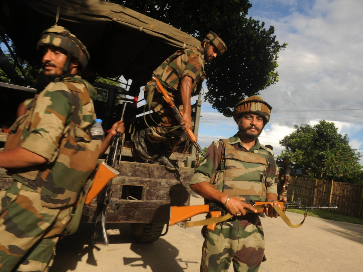 Indian army personnel unload from a truck at Ambadi village in Assam state's Kokrajhar district on July 28, 2012. India's prime minister on July 28 told victims of deadly ethnic riots in the remote northeast it was 'a time for healing' and promised a 'proper inquiry' into the causes of the violence. Premier Manmohan Singh's statements came as police reported five more bodies had been recovered from the conflict in Assam between indigenous Bodo tribes and Muslim settlers over long-running land disputes, pushing the death toll to 50. AFP PHOTO/Diptendu DUTTA / AFP PHOTO / DIPTENDU DUTTA